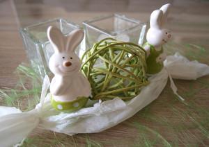 Zwei Porzellan-Osterhasen im Papier-Nest
